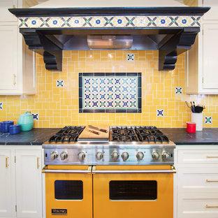 Idéer för ett stort medelhavsstil kök, med luckor med infälld panel, vita skåp, bänkskiva i täljsten, gult stänkskydd, stänkskydd i mosaik, rostfria vitvaror, mellanmörkt trägolv och brunt golv