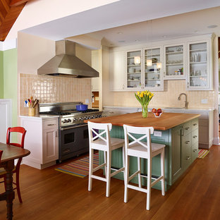 Large country l-shaped eat-in kitchen in Philadelphia with an undermount sink, glass-front cabinets, beige cabinets, marble benchtops, beige splashback, ceramic splashback, coloured appliances, medium hardwood floors and with island.
