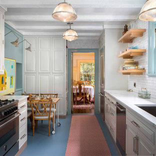 Traditional eat-in kitchen inspiration - Elegant galley blue floor eat-in kitchen photo in Portland with an undermount sink, raised-panel cabinets, white cabinets, white backsplash, stainless steel appliances, no island and white countertops