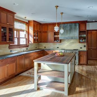 Ispirazione per una cucina a L vittoriana con lavello sottopiano, ante in stile shaker, ante in legno scuro, paraspruzzi beige, elettrodomestici in acciaio inossidabile, pavimento in legno massello medio, isola, pavimento marrone e top grigio