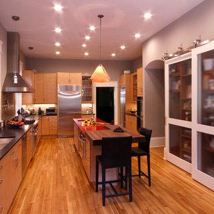 Geschlossene, Mittelgroße Eklektische Küche in U-Form mit Unterbauwaschbecken, hellen Holzschränken, Küchenrückwand in Beige, Rückwand aus Glasfliesen, Küchengeräten aus Edelstahl, Kücheninsel, flächenbündigen Schrankfronten, Granit-Arbeitsplatte und hellem Holzboden in Raleigh