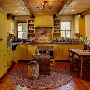 ニューヨークのカントリー風おしゃれなキッチン (黄色いキャビネット、無垢フローリング、アイランドなし、エプロンフロントシンク、カラー調理設備) の写真