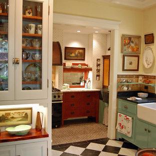 シカゴのシャビーシック調のおしゃれなキッチン (エプロンフロントシンク、フラットパネル扉のキャビネット、青いキャビネット、マルチカラーの床) の写真