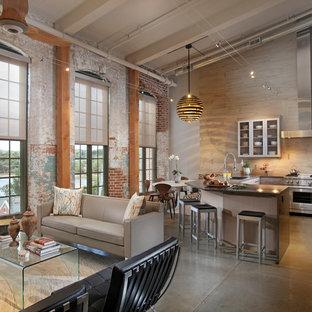 アトランタの中サイズのインダストリアルスタイルのおしゃれなキッチン (アンダーカウンターシンク、フラットパネル扉のキャビネット、珪岩カウンター、ベージュキッチンパネル、シルバーの調理設備の、コンクリートの床、淡色木目調キャビネット、セラミックタイルのキッチンパネル、グレーの床) の写真