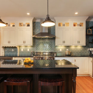 Inspiration for a large traditional l-shaped eat-in kitchen in Raleigh with an undermount sink, shaker cabinets, beige cabinets, granite benchtops, blue splashback, glass tile splashback, stainless steel appliances, medium hardwood floors and with island.