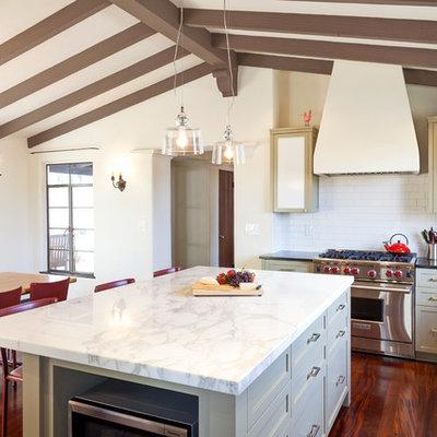 Eat-in kitchen - mediterranean u-shaped eat-in kitchen idea in Los Angeles with shaker cabinets, beige cabinets, white backsplash, subway tile backsplash and stainless steel appliances