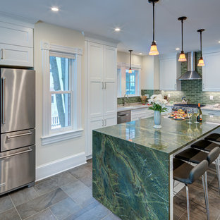 This is an example of a large transitional u-shaped open plan kitchen in DC Metro with an undermount sink, shaker cabinets, white cabinets, marble benchtops, green splashback, subway tile splashback, stainless steel appliances, slate floors, with island, black floor and green benchtop.