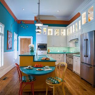 Exemple d'une grand cuisine américaine parallèle exotique avec un évier encastré, un placard à porte shaker, un électroménager en acier inoxydable, un sol en bois brun, un plan de travail en quartz modifié, une crédence bleue, une crédence en mosaïque, un îlot central, des portes de placard blanches et un plan de travail turquoise.