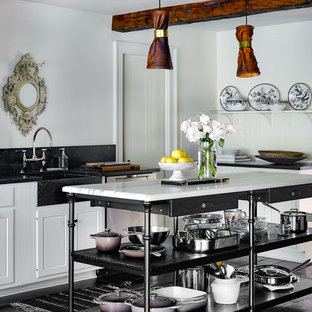 Farmhouse kitchen ideas - Example of a country painted wood floor kitchen design in Chicago with a farmhouse sink, beaded inset cabinets, white cabinets, black backsplash and an island
