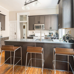 Small minimalist u-shaped medium tone wood floor enclosed kitchen photo in Wilmington with a double-bowl sink, flat-panel cabinets, dark wood cabinets and stainless steel countertops