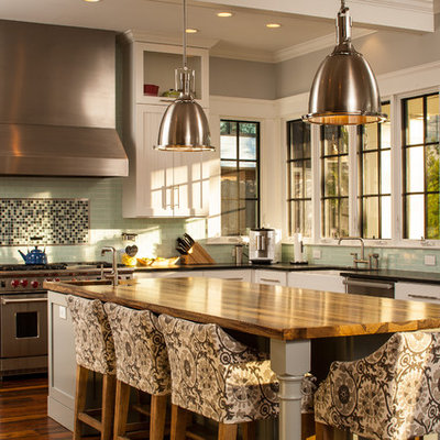 Arts and crafts u-shaped kitchen photo in Atlanta with stainless steel appliances, white cabinets, wood countertops, green backsplash, subway tile backsplash, a farmhouse sink and shaker cabinets