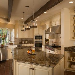 サンフランシスコの大きいトラディショナルスタイルのおしゃれなキッチン (エプロンフロントシンク、レイズドパネル扉のキャビネット、御影石カウンター、茶色いキッチンパネル、石タイルのキッチンパネル、シルバーの調理設備の、白いキャビネット、テラコッタタイルの床、赤い床、ベージュのキッチンカウンター) の写真