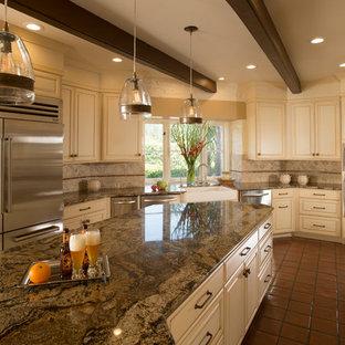 サンフランシスコの広いトラディショナルスタイルのおしゃれなキッチン (エプロンフロントシンク、レイズドパネル扉のキャビネット、御影石カウンター、シルバーの調理設備、白いキャビネット、テラコッタタイルの床、石タイルのキッチンパネル、赤い床、ベージュキッチンパネル、ベージュのキッチンカウンター) の写真