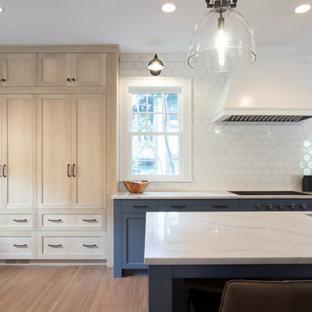 Klassisk inredning av ett mycket stort blå linjärt blått kök och matrum, med en undermonterad diskho, luckor med infälld panel, blå skåp, granitbänkskiva, vitt stänkskydd, stänkskydd i keramik, integrerade vitvaror, mellanmörkt trägolv och en köksö