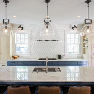 ミネアポリスの巨大なトランジショナルスタイルのおしゃれなキッチン (アンダーカウンターシンク、落し込みパネル扉のキャビネット、青いキャビネット、御影石カウンター、白いキッチンパネル、セラミックタイルのキッチンパネル、パネルと同色の調理設備、無垢フローリング、青いキッチンカウンター) の写真