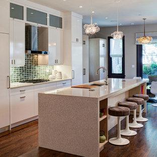 Modern eat-in kitchen in Chicago with a single-bowl sink, flat-panel cabinets, white cabinets, terrazzo benchtops, green splashback, stone tile splashback, white appliances and medium hardwood floors.