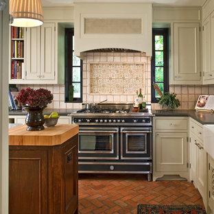 Exempel på ett klassiskt kök, med beige skåp, svarta vitvaror och tegelgolv