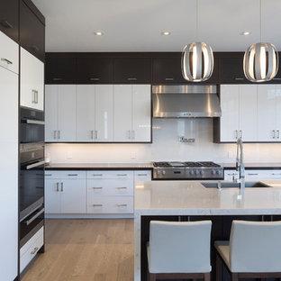 Immagine di una grande cucina moderna con lavello a doppia vasca, ante lisce, ante bianche, top in marmo, paraspruzzi bianco, paraspruzzi in ardesia, elettrodomestici in acciaio inossidabile, parquet chiaro, isola e pavimento giallo