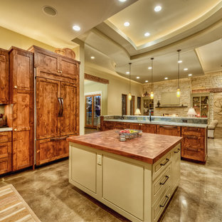 Design ideas for a large traditional u-shaped open plan kitchen in Austin with an undermount sink, recessed-panel cabinets, dark wood cabinets, marble benchtops, multi-coloured splashback, stainless steel appliances, concrete floors, multiple islands, slate splashback and grey floor.
