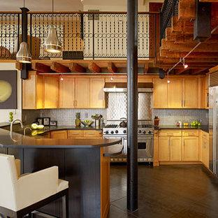 ニューヨークの大きいエクレクティックスタイルのおしゃれなキッチン (エプロンフロントシンク、落し込みパネル扉のキャビネット、淡色木目調キャビネット、御影石カウンター、メタリックのキッチンパネル、メタルタイルのキッチンパネル、シルバーの調理設備の、コンクリートの床、黒い床、黒いキッチンカウンター) の写真