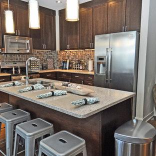 Offene, Mittelgroße Moderne Küche in L-Form mit Unterbauwaschbecken, Schrankfronten im Shaker-Stil, braunen Schränken, Granit-Arbeitsplatte, Küchenrückwand in Beige, Rückwand aus Glasfliesen, Küchengeräten aus Edelstahl, dunklem Holzboden und Kücheninsel in Omaha