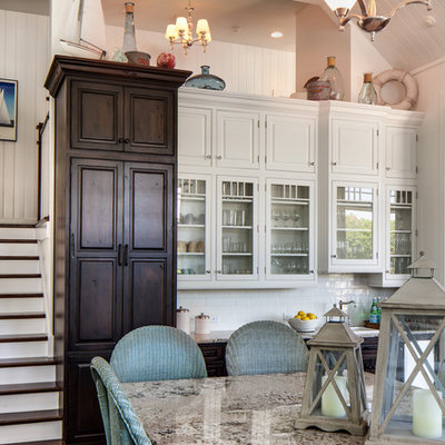 Inspiration for a mid-sized timeless u-shaped brown floor and medium tone wood floor eat-in kitchen remodel in Dallas with glass-front cabinets, white cabinets, white backsplash, subway tile backsplash, a farmhouse sink, granite countertops, paneled appliances, an island and gray countertops