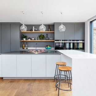 This is an example of a medium sized contemporary single-wall kitchen in London with flat-panel cabinets, stainless steel appliances, light hardwood flooring and an island.