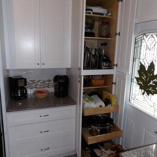 他の地域の中くらいのトランジショナルスタイルのおしゃれなキッチン (アンダーカウンターシンク、シェーカースタイル扉のキャビネット、白いキャビネット、御影石カウンター、白いキッチンパネル、サブウェイタイルのキッチンパネル、シルバーの調理設備、淡色無垢フローリング、アイランドなし) の写真