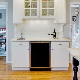 Klassische Küche in L-Form mit Unterbauwaschbecken, Schrankfronten im Shaker-Stil, weißen Schränken, Granit-Arbeitsplatte, Küchenrückwand in Weiß, Rückwand aus Metrofliesen, Küchengeräten aus Edelstahl, hellem Holzboden und Kücheninsel in Boston