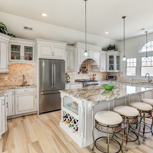 Inspiration for a large beach style l-shaped open plan kitchen in New York with an undermount sink, raised-panel cabinets, beige cabinets, granite benchtops, beige splashback, travertine splashback, stainless steel appliances, porcelain floors, with island, beige floor and beige benchtop.