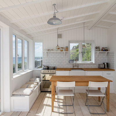 Example of a mid-sized beach style single-wall light wood floor eat-in kitchen design in Cornwall with a farmhouse sink, white cabinets, white backsplash, subway tile backsplash, stainless steel appliances, shaker cabinets and wood countertops