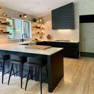 Große Moderne Wohnküche in U-Form mit Landhausspüle, flächenbündigen Schrankfronten, schwarzen Schränken, Marmor-Arbeitsplatte, Küchenrückwand in Weiß, Rückwand aus Terrakottafliesen, Küchengeräten aus Edelstahl, hellem Holzboden, beigem Boden und weißer Arbeitsplatte in New York