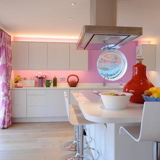 Modelo de cocina actual con fregadero bajoencimera, armarios con paneles lisos, puertas de armario blancas, salpicadero rosa y suelo de madera clara