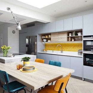 Modelo de cocina comedor contemporánea, grande, con armarios con paneles lisos, puertas de armario grises, salpicadero amarillo, salpicadero de azulejos de cerámica, una isla y encimeras blancas