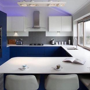 コーンウォールの小さいコンテンポラリースタイルのおしゃれなキッチン (シングルシンク、フラットパネル扉のキャビネット、白いキャビネット、ラミネートカウンター、クッションフロア) の写真