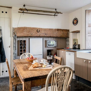 Design ideas for a rural kitchen/diner in Sussex with a belfast sink, brown cabinets, wood worktops, white appliances and no island.