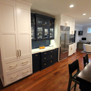 Expansive transitional u-shaped eat-in kitchen in DC Metro with a farmhouse sink, flat-panel cabinets, blue cabinets, quartzite benchtops, green splashback, glass tile splashback, stainless steel appliances, medium hardwood floors, with island and red floor.
