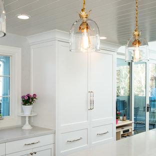 ソルトレイクシティの大きいシャビーシック調のおしゃれなキッチン (エプロンフロントシンク、フラットパネル扉のキャビネット、白いキャビネット、クオーツストーンカウンター、白いキッチンパネル、大理石の床、パネルと同色の調理設備、無垢フローリング、茶色い床、白いキッチンカウンター) の写真