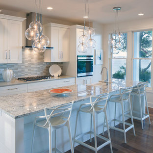 Design ideas for a classic single-wall open plan kitchen in Grand Rapids with a belfast sink, recessed-panel cabinets, white cabinets, granite worktops, integrated appliances and an island.