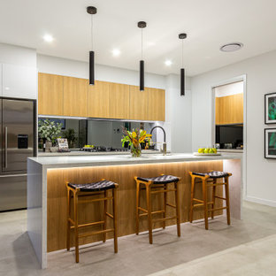 Design ideas for a large contemporary l-shaped kitchen in Brisbane with an undermount sink, flat-panel cabinets, medium wood cabinets, mirror splashback, stainless steel appliances, with island, grey floor and grey benchtop.