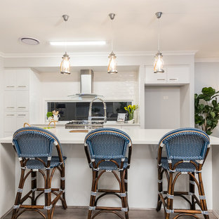 Photo of a large beach style kitchen in Brisbane with flat-panel cabinets, white cabinets, quartz benchtops, white benchtop, window splashback, dark hardwood floors and with island.
