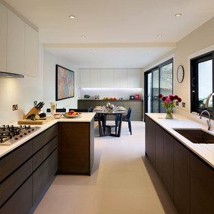 ロンドンの大きいヴィクトリアン調のおしゃれなキッチン (ダブルシンク、フラットパネル扉のキャビネット、濃色木目調キャビネット、御影石カウンター、白いキッチンパネル、石スラブのキッチンパネル、パネルと同色の調理設備、セラミックタイルの床) の写真