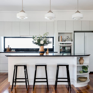 This is an example of a mid-sized contemporary l-shaped kitchen in Brisbane with white cabinets, black splashback, medium hardwood floors and an island.