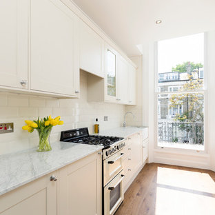 Inspiration for a small country separate kitchen in London with shaker cabinets, white cabinets, white splashback, subway tile splashback, stainless steel appliances and medium hardwood floors.