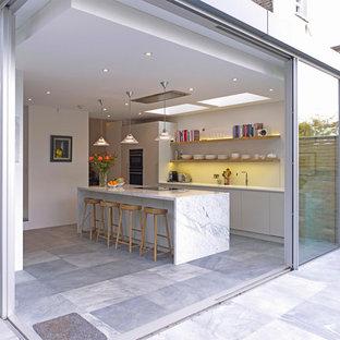 Zweizeilige, Große Moderne Küche mit flächenbündigen Schrankfronten, grauen Schränken, Marmor-Arbeitsplatte, Küchenrückwand in Weiß, Glasrückwand, schwarzen Elektrogeräten, Keramikboden und Kücheninsel in London