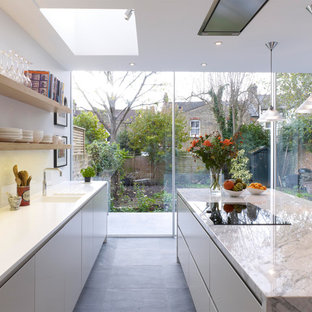 This is an example of a large contemporary galley open plan kitchen in London with an integrated sink, flat-panel cabinets, grey cabinets, marble benchtops, white splashback, glass sheet splashback, ceramic floors and with island.