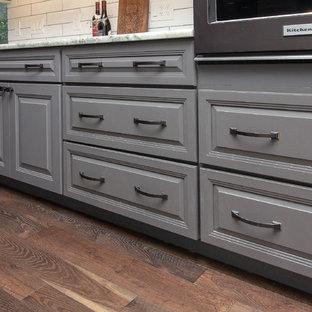 ヒューストンの大きいシャビーシック調のおしゃれなキッチン (アンダーカウンターシンク、レイズドパネル扉のキャビネット、グレーのキャビネット、御影石カウンター、白いキッチンパネル、サブウェイタイルのキッチンパネル、黒い調理設備、無垢フローリング、茶色い床、グレーのキッチンカウンター) の写真