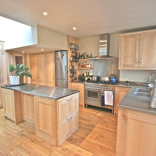 Photo of a large traditional l-shaped kitchen in London with an integrated sink, shaker cabinets, light wood cabinets, stainless steel benchtops, metallic splashback, stainless steel appliances, light hardwood floors and with island.