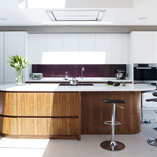 Design ideas for a contemporary kitchen in London with flat-panel cabinets, white cabinets, glass sheet splashback, stainless steel appliances and an island.