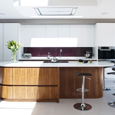 Kitchen - contemporary kitchen idea in London with flat-panel cabinets, white cabinets, glass sheet backsplash, stainless steel appliances and an island